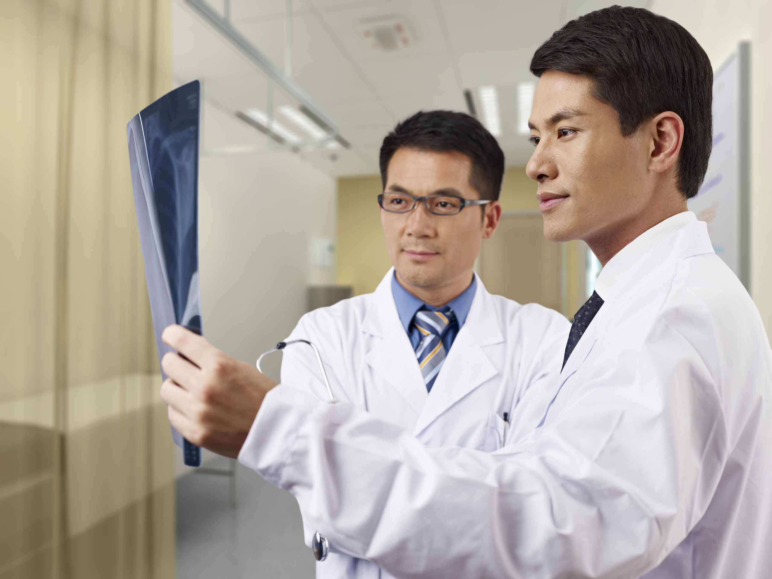 two asian doctors looking at x-ray film in consultation room.