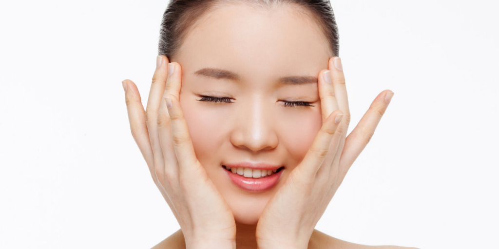girl touching her face with eyes closed for skin care